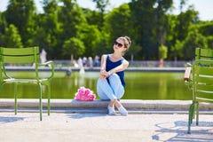 Giovane donna parigina delle peonie rosa in Tuileries immagini stock