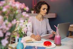 Giovane donna pensierosa che fa compito con il computer portatile Immagini Stock Libere da Diritti