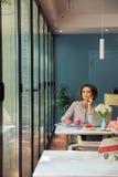 Giovane donna pensierosa che fa compito con il computer portatile Fotografia Stock