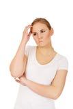 Giovane donna pensierosa che graffia la sua testa Fotografia Stock