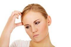 Giovane donna pensierosa che graffia la sua testa Fotografie Stock Libere da Diritti