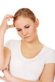 Giovane donna pensierosa che graffia la sua testa Fotografia Stock Libera da Diritti