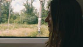 Giovane donna pensierosa che guarda da una finestra del treno Viaggio, concetto di trasporto video d archivio
