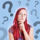Giovane donna pensierosa con i segni di interrogazione fotografia stock
