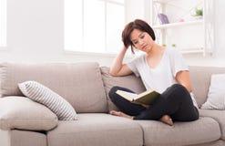 Giovane donna pensierosa con un libro Fotografia Stock