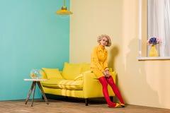 giovane donna pensierosa in retro abbigliamento che si siede sul sofà giallo all'appartamento variopinto, bambola Immagini Stock