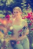 Giovane donna piacevole che lavora con le rose del cespuglio con lo strumento orticolo immagini stock