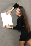 Giovane donna piacevole con un foglio di carta vuoto bianco Fotografia Stock Libera da Diritti