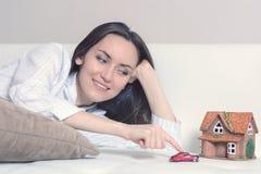Giovane donna in pigiami che si trovano su un sofà bianco in una stanza davanti ad una casa di Wendy e un'automobile e sogni di u fotografie stock libere da diritti