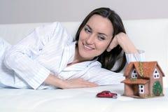 Giovane donna in pigiami che si trovano su un sofà bianco in una stanza davanti ad una casa di Wendy e un'automobile e sogni di u fotografia stock