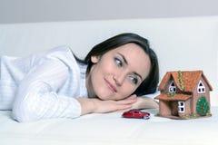 Giovane donna in pigiami che si trovano su un sofà bianco in una stanza davanti ad una casa di Wendy e un'automobile e sogni di u fotografia stock libera da diritti