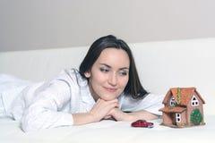 Giovane donna in pigiami che si trovano su un sofà bianco in una stanza davanti ad una casa di Wendy e un'automobile e sogni di u fotografie stock
