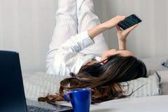 Giovane donna in pigiami che si trovano sul letto, piedi sulla parete Comunicazione nelle reti sociali, Smart Phone di uso Immagini Stock Libere da Diritti