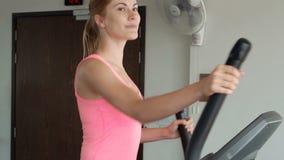 Giovane donna positiva allegra di bella misura in palestra che fa gli esercizi sul risolvere ellittico dell'istruttore video d archivio