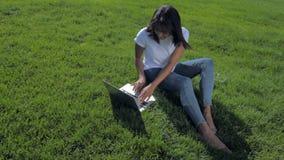 Giovane donna positiva che lavora al computer portatile in parco archivi video