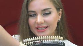 Giovane donna positiva che sceglie tono dei denti in clinica archivi video