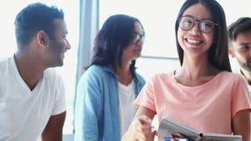 Giovane donna positiva che spende tempo con i suoi colleghi studenti archivi video