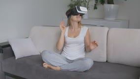Giovane donna positiva in salone che indossa la cuffia avricolare di VR che guarda un video da 360 gradi Metraggio nella risoluzi archivi video