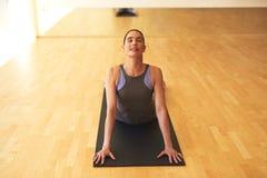 Giovane donna premurosa che allunga sulla stuoia di yoga Fotografia Stock