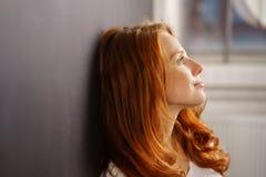 Giovane donna premurosa che si appoggia una parete Fotografia Stock