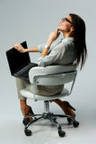 Giovane donna premurosa che si siede con il computer portatile e cercare Fotografia Stock Libera da Diritti