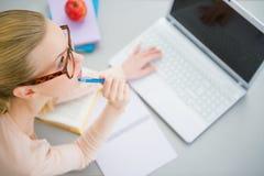 Giovane donna premurosa che studia nella cucina Fotografia Stock