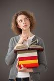 Giovane donna premurosa che tiene una pila di libri Fotografia Stock