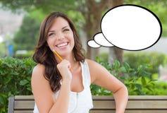 Giovane donna premurosa con la matita e la bolla in bianco di pensiero Immagini Stock
