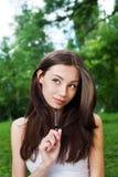 Giovane donna premurosa con la penna fuori in parco Immagini Stock