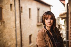 Giovane donna premurosa graziosa sul balcone in una città antica immagine stock libera da diritti