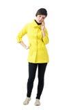 Giovane donna preoccupata in cappotto giallo che parla sul telefono che guarda giù immagini stock libere da diritti