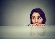 Giovane donna preoccupata che esamina qualcosa che dà una occhiata da sotto la tavola Fotografie Stock