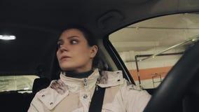 Giovane donna preoccupata in rivestimento bianco che determina parcheggio sotterraneo della depressione dell'automobile video d archivio