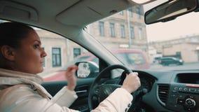 Giovane donna preoccupata in rivestimento bianco che guida la via della città della depressione dell'automobile video d archivio