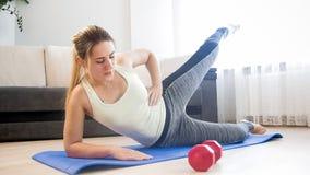 Giovane donna profondamente che respira mentre facendo esercizio di forma fisica a casa Fotografia Stock Libera da Diritti