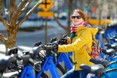 Giovane donna pronta ad affittare una bici a New York fotografie stock