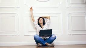 Giovane donna, ragazza, castane, in camicia bianca e jeans, ascoltanti la musica, facendo uso delle cuffie e del computer portati archivi video