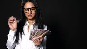 Giovane donna ricca che getta i suoi soldi su fondo nero archivi video