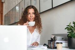 Giovane donna riccia che si siede dalla tavola con il computer portatile Immagini Stock