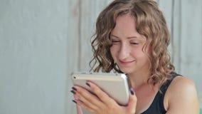 Giovane donna riccia che si siede sul letto con il pc della compressa archivi video