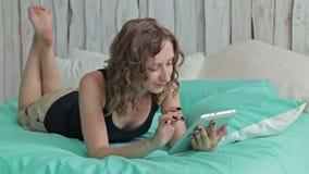 Giovane donna riccia che si trova nel letto con il pc della compressa Colpo del carrello video d archivio