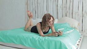Giovane donna riccia che si trova nel letto con il pc della compressa Colpo del carrello stock footage