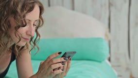Giovane donna riccia che si trova nel letto con lo smartphone Colpo del carrello stock footage