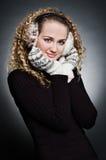 Giovane donna riccia in pellicce trasduttore auricolare e guanto fotografie stock