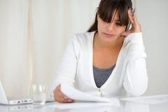 Giovane donna riflettente che lavora con i documenti fotografie stock