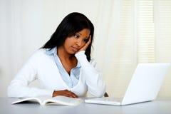 Giovane donna riflettente che studia sul computer portatile Fotografia Stock