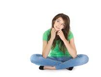 Giovane donna riflettente isolata che si siede con le gambe attraversate. Fotografie Stock Libere da Diritti