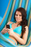 Giovane donna rilassata che esamina telefono cellulare dentro Fotografie Stock