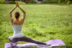 Giovane donna rilassata che fa yoga all'aperto Fotografie Stock