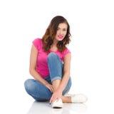 Giovane donna rilassata che si siede su un pavimento Fotografia Stock